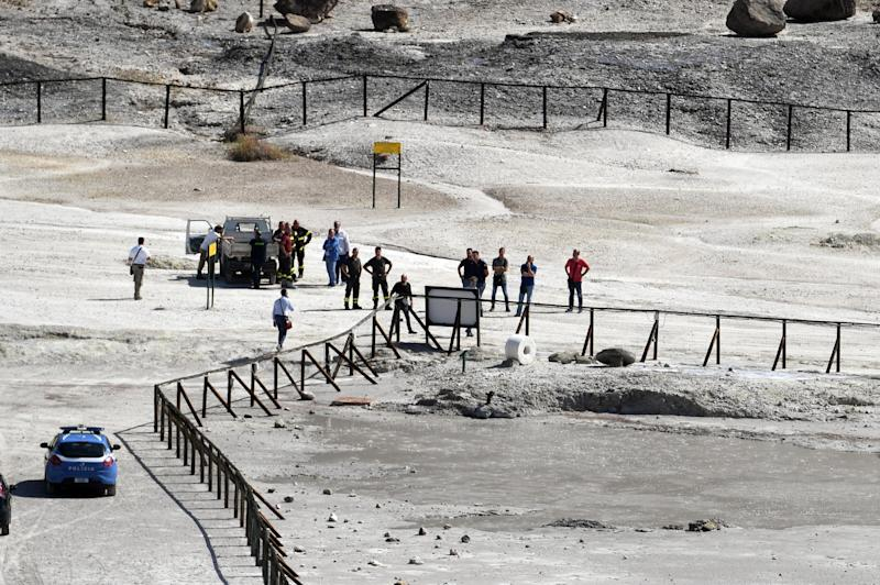 Rescuers stand on the site where three people reportedly died when they fell into a crater in a steamy volcanic field in Pozzuoli, near Naples, Italy, Tuesday, Sept. 12, 2017. Italian news reports say an 11-year-old Italian boy and his parents died in a steamy volcanic field near Naples. ANSA said the parents tried to rescue the boy after he entered an off-limits area at the Solfatara Crater in Pozzuoli, and was overcome by gases, losing consciousness. (Ciro Fusco/ANSA via AP)