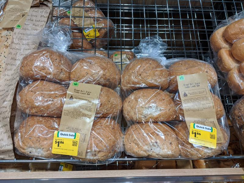 Photo shows fresh backed Woolworths bakery buns on shelf with reduced stickers.
