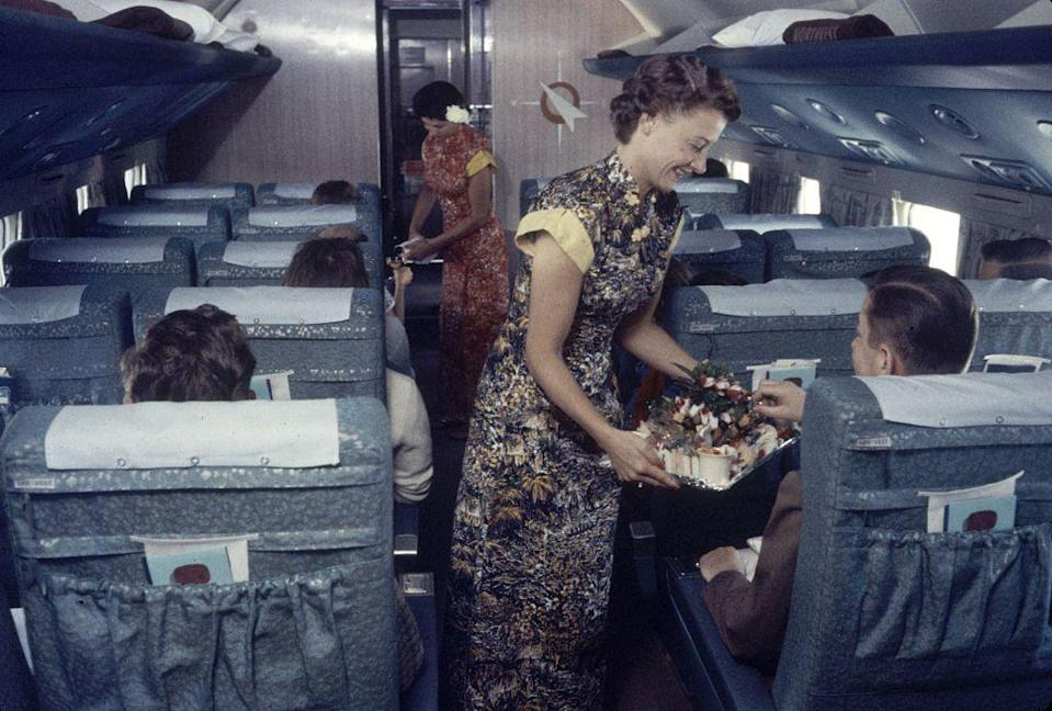 "<p>In-flight meals <a href=""https://www.washingtonpost.com/travel/2019/10/17/golden-age-airplane-food-is-over-future-snacks-sustainability/"" rel=""nofollow noopener"" target=""_blank"" data-ylk=""slk:became common (and more elaborate) in the Golden Age"" class=""link rapid-noclick-resp"">became common (and more elaborate) in the Golden Age</a>, replacing the frozen foods and minimal variety of earlier years, according to the<em> Washington Post.</em> Here, a pair of flight attendants serves refreshments on a Japan Air Lines flight from San Francisco to Tokyo. </p>"