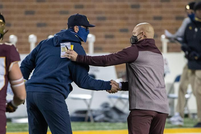 Michigan coach Jim Harbaugh and Minnesota coach P. J. Fleck shake hands after the 49-24 win by the Wolverines at TCF Bank Stadium, Oct. 24, 2020.