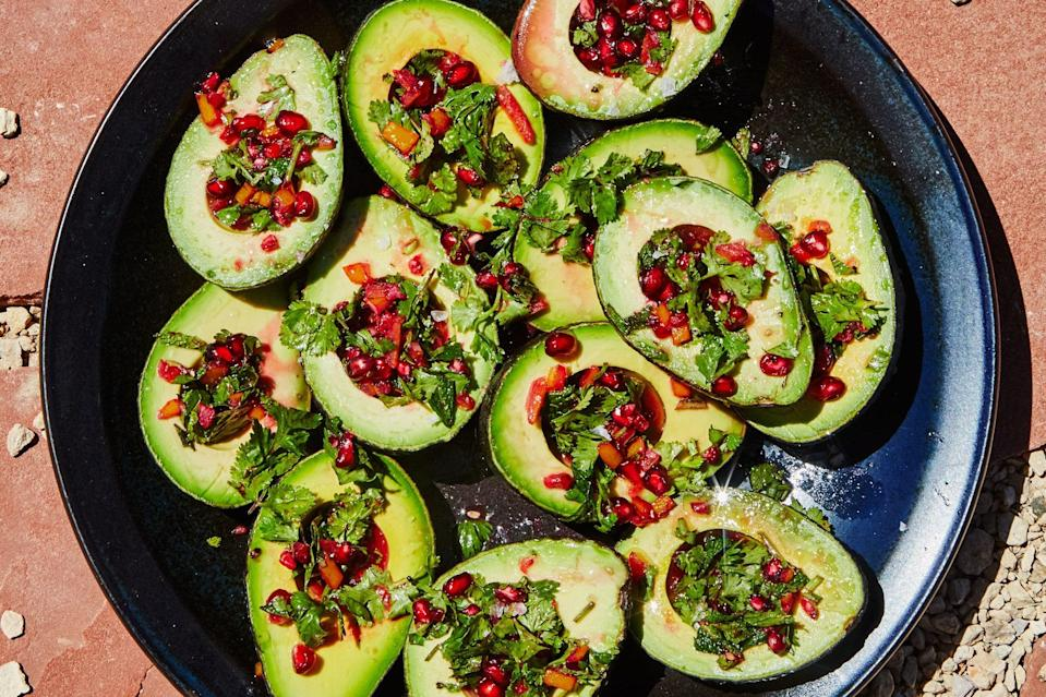 """These avocado cups look too good to eat (almost). This delicious—but simple—avocado recipe features a bright salsa made from cilantro, oil, lemon juice, mint, pomegranate seeds, and lemon peel. <a href=""""https://www.epicurious.com/recipes/food/views/avocado-cups-with-pomegranate-salsa-verde?mbid=synd_yahoo_rss"""" rel=""""nofollow noopener"""" target=""""_blank"""" data-ylk=""""slk:See recipe."""" class=""""link rapid-noclick-resp"""">See recipe.</a>"""