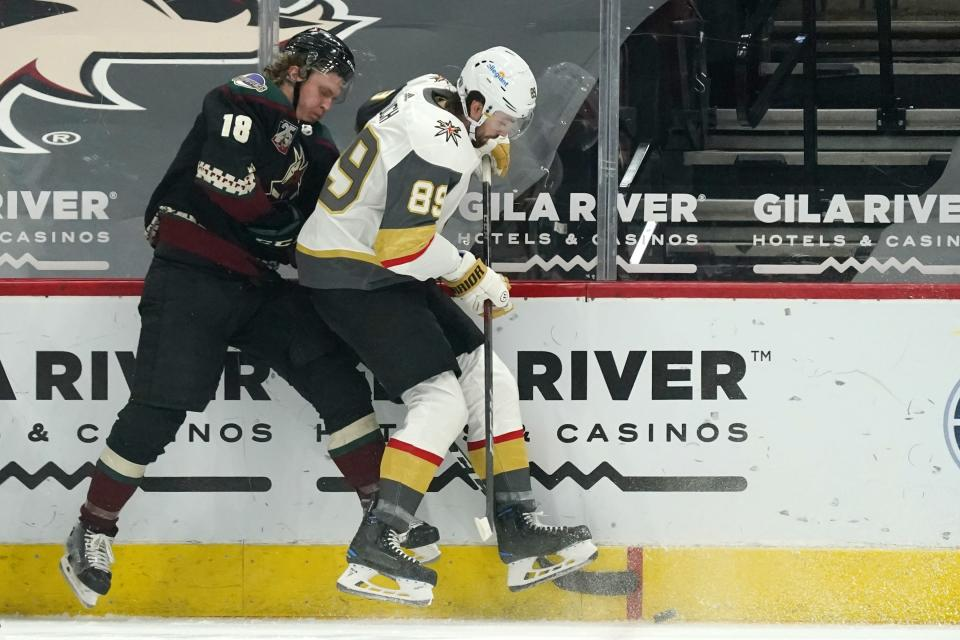 Arizona Coyotes center Christian Dvorak (18) battles with Vegas Golden Knights right wing Alex Tuch (89) for the puck during the first period of an NHL hockey game Friday, Jan. 22, 2021, in Glendale, Ariz. (AP Photo/Ross D. Franklin)