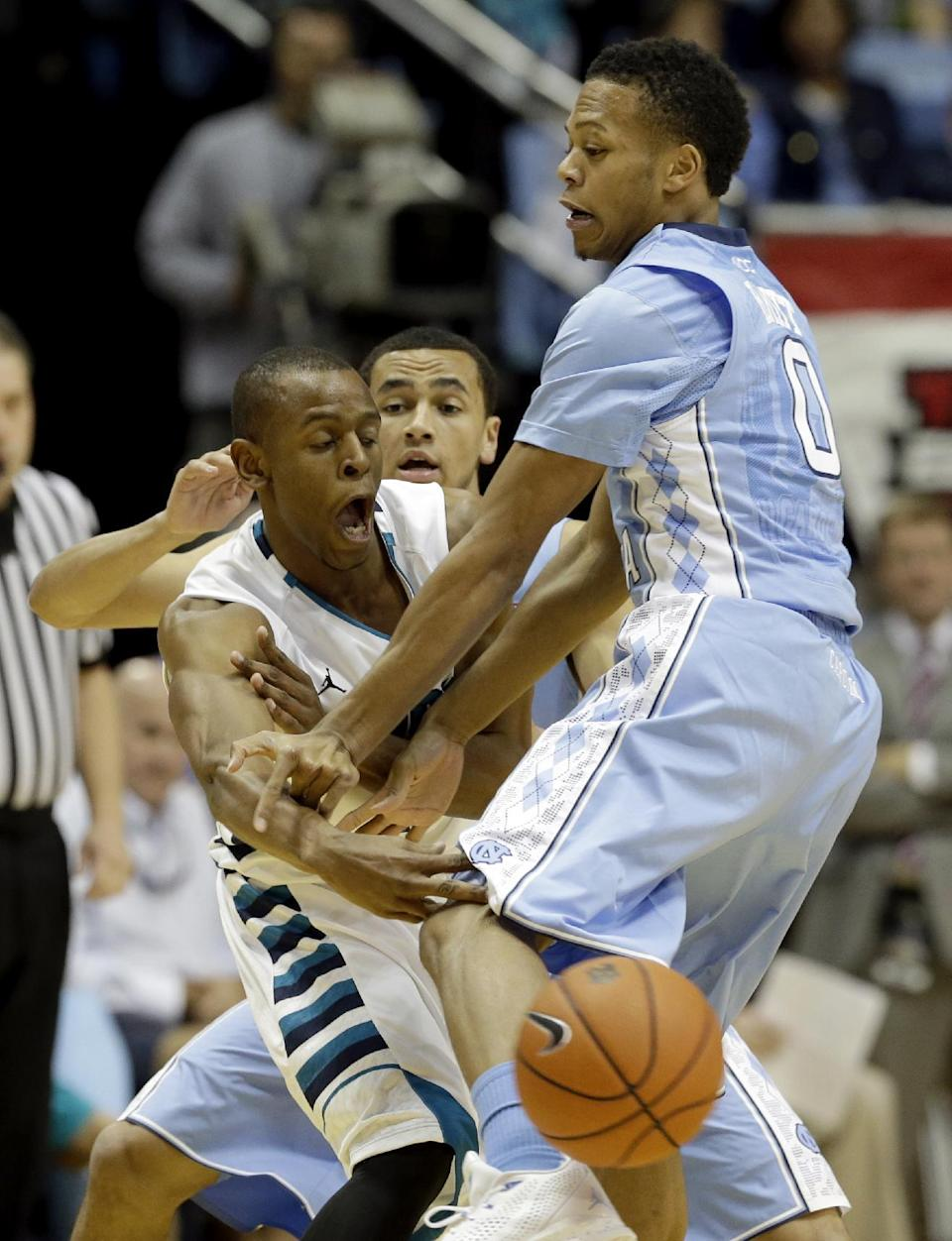 North Carolina's Nate Britt (0) and Marcus Paige, rear, guard UNC Wilmington's Freddie Jackson during the first half of an NCAA college basketball game in Chapel Hill, N.C., Tuesday, Dec. 31, 2013. (AP Photo/Gerry Broome)