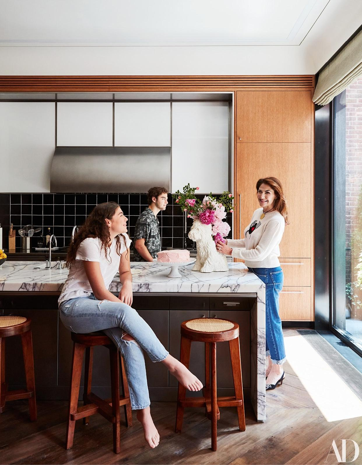 """<div class=""""caption""""> Allison, wearing a Dior sweater and jeans, and two of her children gather around the kitchen island; fashion styling by Marina Muñoz. </div>"""
