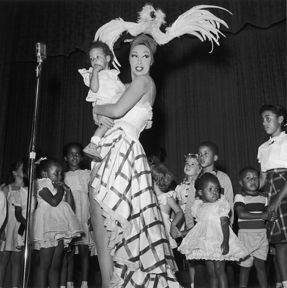 <p>Baker stands on stage with children at a performance in Los Angeles dressed in a striped and ruffled skirt and feathered turban decorated with a rooster and chicken that make for a statement-making ensemble.<br></p>