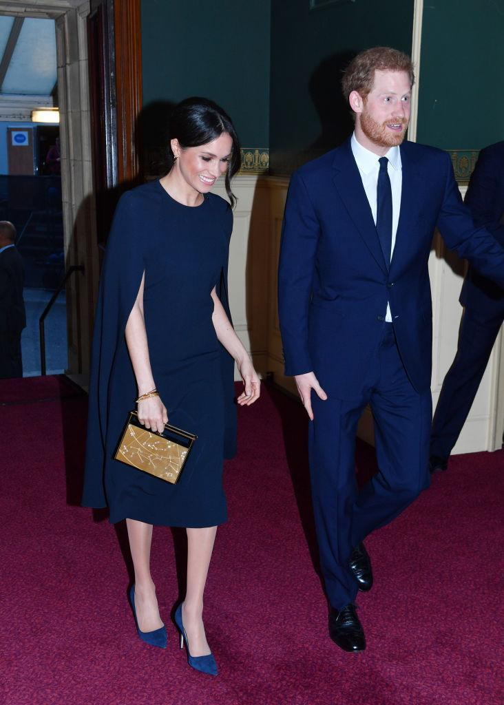 <p>To celebrate the Queen's 92nd birthday, Prince Harry and Meghan Markle colour co-ordinated for the first time. The former actress donned a navy-hued cape dress by Stella McCartney (with a £1,150 price tag) as she joined the royal family at the Royal Albert Hall. She accessorised the look with a Naeem Khan Armory Zodiac clutch. <em>[Photo: Getty]</em> </p>