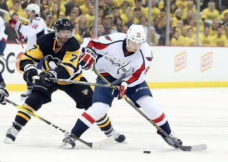 Washington Capitals left wing Andre Burakovsky (65) carries the puck against pressure from Pittsburgh Penguins center Matt Cullen (7) during the third period in game three of the second round of the 2016 Stanley Cup Playoffs at the CONSOL Energy Center. The Pens won 3-2. Mandatory Credit: Charles LeClaire-USA TODAY Sports