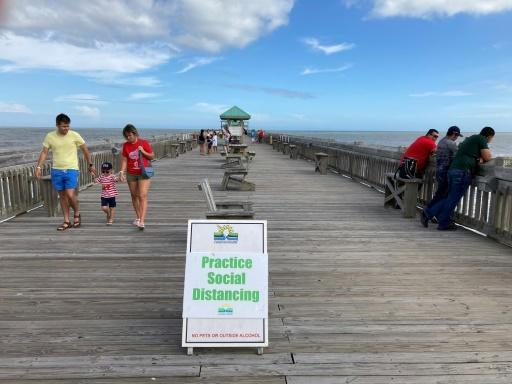 People walk on the pier at Folly Beach on May 17 near Charleston, South Carolina, a state which reopened a bit later than neighboring Georgia
