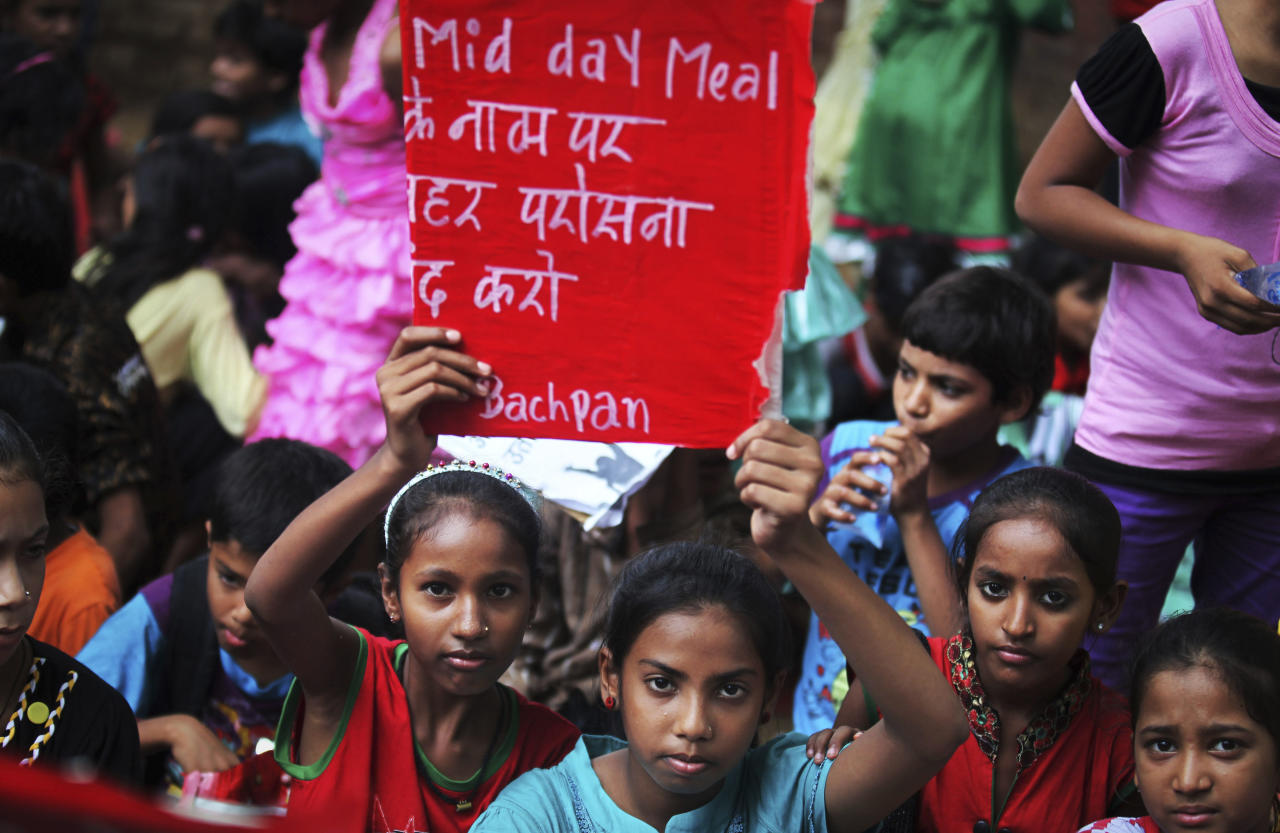 """Indian children hold placards as they participate in a protest organized by non-governmental organization Bachpan Bachao Andolan, or Save Childhood Movement, against the death of schoolchildren after eating free midday meal served at a school, in New Delhi, India, Saturday, July 20, 2013. Police said samples of cooking oil and leftover food taken from an Indian school where 23 children died after eating lunch this past week were contaminated with """"very toxic"""" levels of an agricultural pesticide. The placard reads """"Stop serving poison in the name of mid-day meals."""" (AP Photo/Altaf Qadri)"""