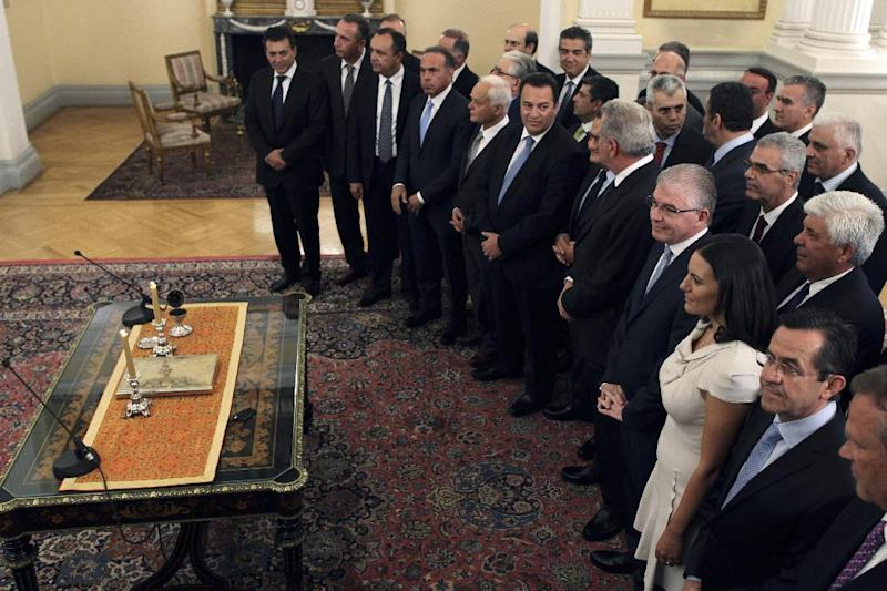FILE - In this Thursday, June 21, 2012 file photo, deputy labor minister Nikos Nikolopoulos, first row second left, takes part with other Greek new cabinet ministers in a swearing-in ceremony at the Presidential palace in Athens. Nikolopoulos resigned on Monday July 9, 2012 from Greece's new coalition government, saying it should have pressed harder to renegotiate the terms of the country's bailout agreements. (AP Photo/Petros Giannakouris, file)