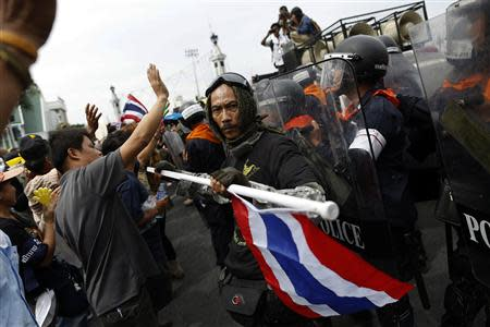 A protester holds a Thai national flag as others face police during a rally against an amnesty bill, on the main road near the government and parliament buildings in central Bangkok November 7, 2013. REUTERS/Damir Sagolj