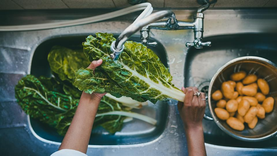 Cropped shot of a woman rinsing spinach in a kitchen sink at home.