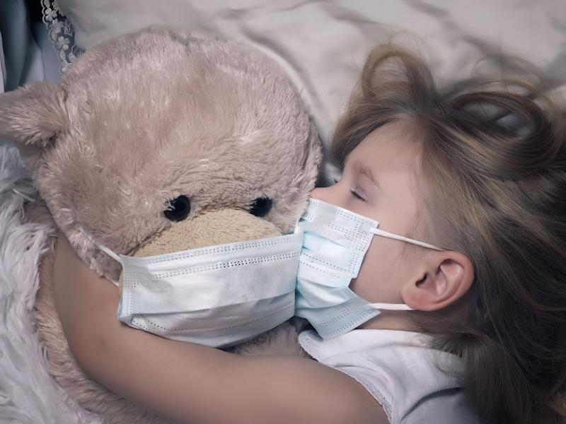 Little girl and big plush bear sleep in medical masks. The concept of childhood diseases, empathy, support and help sick children (Photo: kozorog via Getty Images)