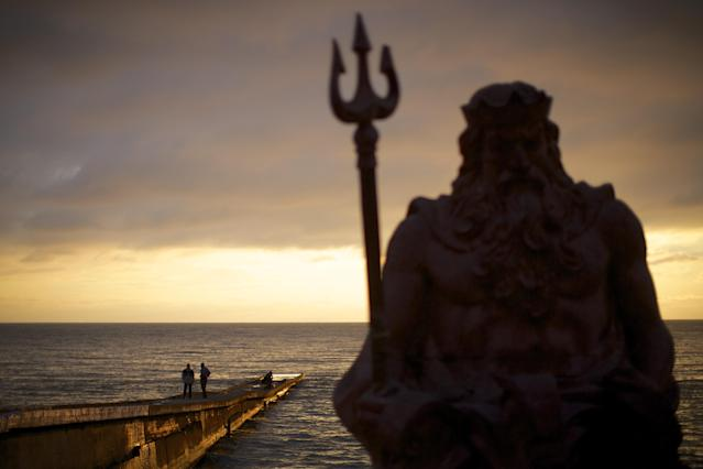 In this photo taken on Thursday, Nov. 28, 2013, the statue of ancient Roman god Neptune sits in guard of the beach during the sunset at an embankment of Sochi, Russia. As the Winter Games are getting closer, many Sochi residents are complaining that their living conditions only got worse and that authorities are deaf to their grievances. (AP Photo/Alexander Zemlianichenko)