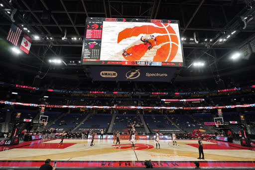 The Toronto Raptors and the Miami Heat tip off to start during the first half of an NBA preseason basketball game Friday, Dec. 18, 2020, in Tampa, Fla. The Raptors are playing their home games in Tampa as a result of Canada's strict travel regulations stemming from the coronavirus pandemic. (AP Photo/Chris O'Meara)