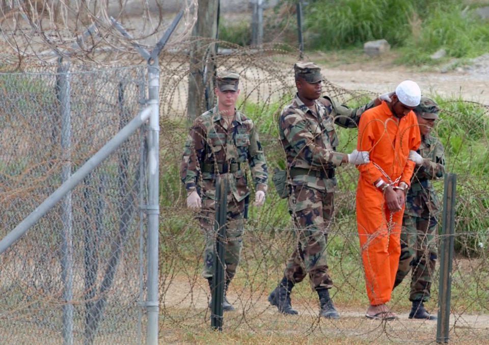 FILE - In this Feb. 6, 2002, file photo a detainee is led by military police to be interrogated by military officials at Camp X-Ray at the U.S. Naval Base at Guantanamo Bay, Cuba. At the time the image was taken there were 158 al-Qaida and Taliban prisoners being held at Camp X-Ray. The White House says it intends to shutter the prison on the U.S. base in Cuba, which opened in January 2002 and where most of the 39 men still held have never been charged with a crime. (AP Photo/Lynne Sladky, File)