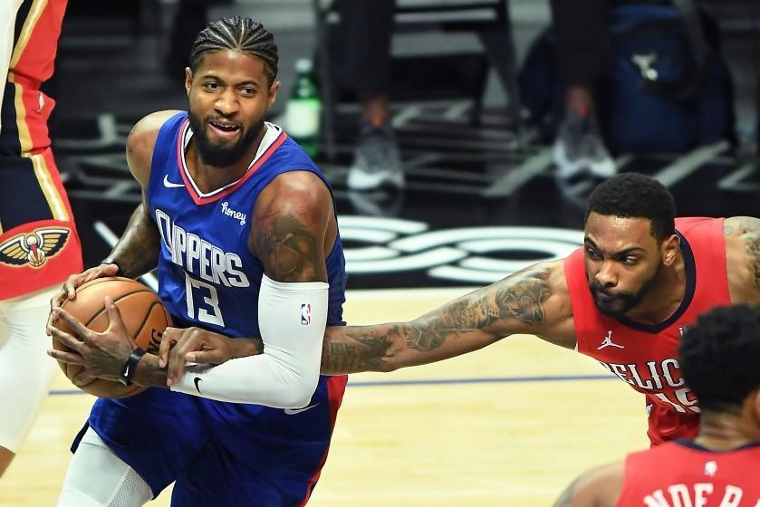 LOS ANGELES, CALIFORNIA JANUARY 13, 2021-Clippers Paul George is fouled by Pelicans Sindarius Thornwell in the 1st quarter at the Staples Center Wednesday. (Los Angeles Times/Wally Skalij)