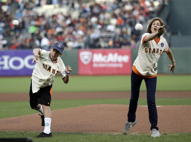 Aaron Hern, left, and Amanda North both survivors of the Boston marathon bombings throw out the ceremonial first pitch before a baseball game between the San Francisco Giants and the Boston Red Sox on Monday, Aug. 19, 2013, in San Francisco. (AP Photo/Marcio Jose Sanchez)