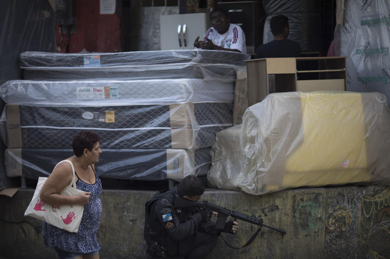 A woman walks past police officer as he takes position during an operation at the Rocinha slum in Rio de Janeiro, Brazil, Friday, Sept. 22, 2017. Shootouts have erupted in several areas of Rio de Janeiro, prompting Brazilian authorities to shut roads and close schools. (AP Photo/Leo Correa)