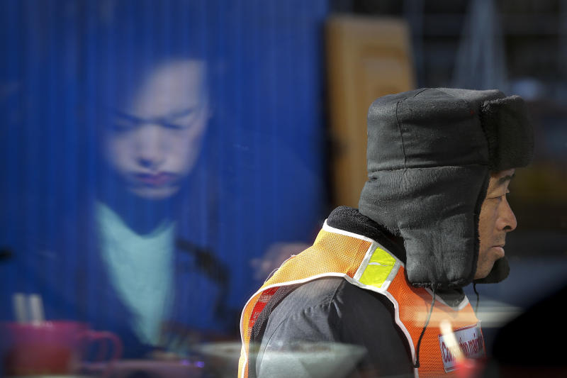 In this Tuesday, Jan. 15, 2019, file photo, a construction worker walks by a woman eating her lunch as she is reflected on a restaurant's window in Beijing. China plans to slash taxes, step up spending and provide ample financing to private and small enterprises to help counter the country's worst slowdown since the global financial crisis and the impact of a bruising trade war with the U.S. (AP Photo/Andy Wong, File)