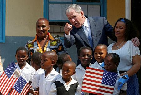 Former US President George W. Bush greets children at a school in Gaborone