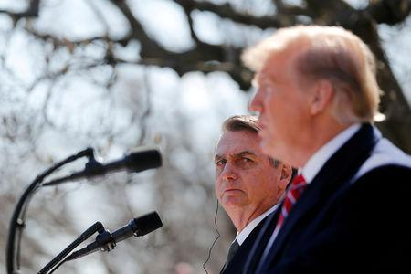 FILE PHOTO: Brazilian President Jair Bolsonaro listens to U.S. President Donald Trump during a joint news conference in the Rose Garden of the White House in Washington, U.S., March 19, 2019. REUTERS/Carlos Barria/File Photo