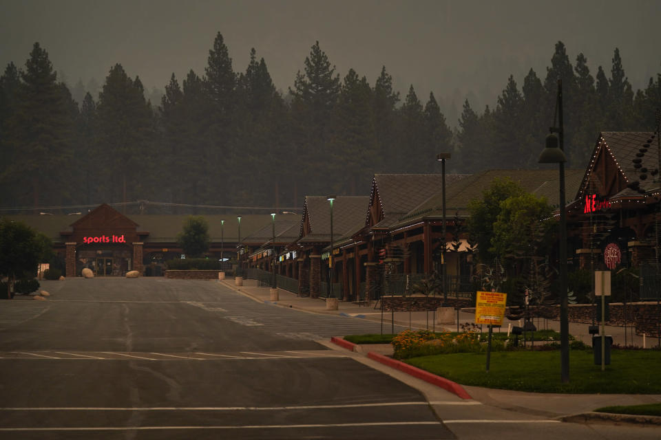 FILE - In this Tuesday, Aug. 31, 2021, file photo, a shopping mall is empty after a mandatory evacuation was ordered due to the Caldor Fire in South Lake Tahoe, Calif. State fire officials said evacuation orders for the area were reduced to warnings as of 3 p.m. on Sunday, Sept. 5. Some 22,000 people had been forced to flee the popular resort and nearby areas last week as the Caldor Fire roared toward it. (AP Photo/Jae C. Hong, File)