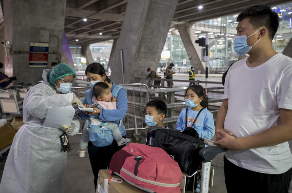 A public health worker gathers information from Chinese tourists from Shanghai, who arrived at Suvarnabhumi airport on special tourist visas, in Bangkok, Thailand, Tuesday, Oct. 20, 2020. Thailand on Tuesday took a modest step toward reviving its coronavirus-battered tourist industry by welcoming 39 visitors who flew in from Shanghai, the first such arrival since normal traveler arrivals were banned almost seven months ago. (AP Photo/Wason Wanichakorn)
