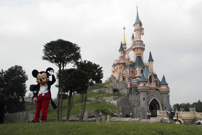 FILE - In this June 8, 2018 file photo, a person dressed as Mickey Mouse poses in front of the castle of Sleeping Beauty at Disneyland Paris, in Chessy, France, east of Paris. The French tourist industry received a further boost Wednesday, July 15, 2020 with the partial reopening of Disneyland Paris and the opening up of the top floor of the Eiffel Tower. Disneyland Paris, Europe's most frequented theme park resort, is partially re-opening to the public, four months after it closed as a result of the coronavirus pandemic. (AP Photo/Francois Mori, File)