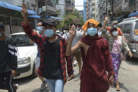 A Buddhist monk joins anti-coup protesters as they flash the three-finger salute of defiance during a demonstration in Yangon, Myanmar on Tuesday April 27, 2021. Demonstrations have continued in many parts of the country since Saturday's meeting of leaders from the Association of Southeast Asian Nations, as have arrests and beatings by security forces despite an apparent agreement by junta leader Senior Gen. Min Aung Hlaing to end the violence. (AP Photo)