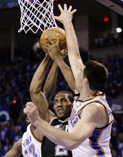 San Antonio Spurs small forward Kawhi Leonard, center, is defended by Oklahoma City Thunder's James Harden (13) and Nick Collison (4) during the first half of Game 3 in their NBA basketball Western Conference finals playoff series, Thursday, May 31, 2012, in Oklahoma City. (AP Photo/Eric Gay)