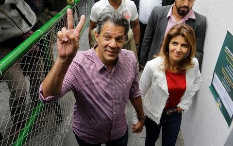 Workers' Party presidential candidate Fernando Haddad, accompanied by his wife Ana Estela, arrives at a polling station to cast his vote - Credit: AP