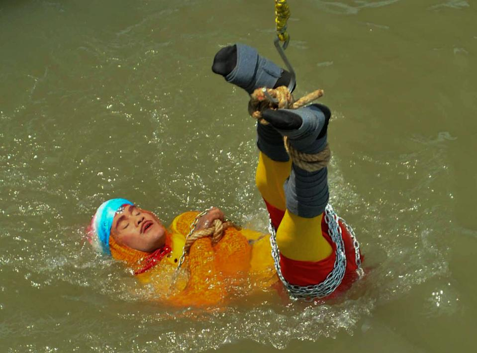 The magician known as Wizard Mandrake being lowered into Hooghly river.
