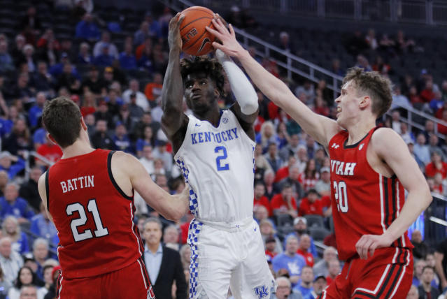 Kentucky's Kahlil Whitney (2) tries to shoot between Utah's Riley Battin, left, and Mikael Jantunen during the second half of an NCAA college basketball game Wednesday, Dec. 18, 2019, in Las Vegas. (AP Photo/John Locher)