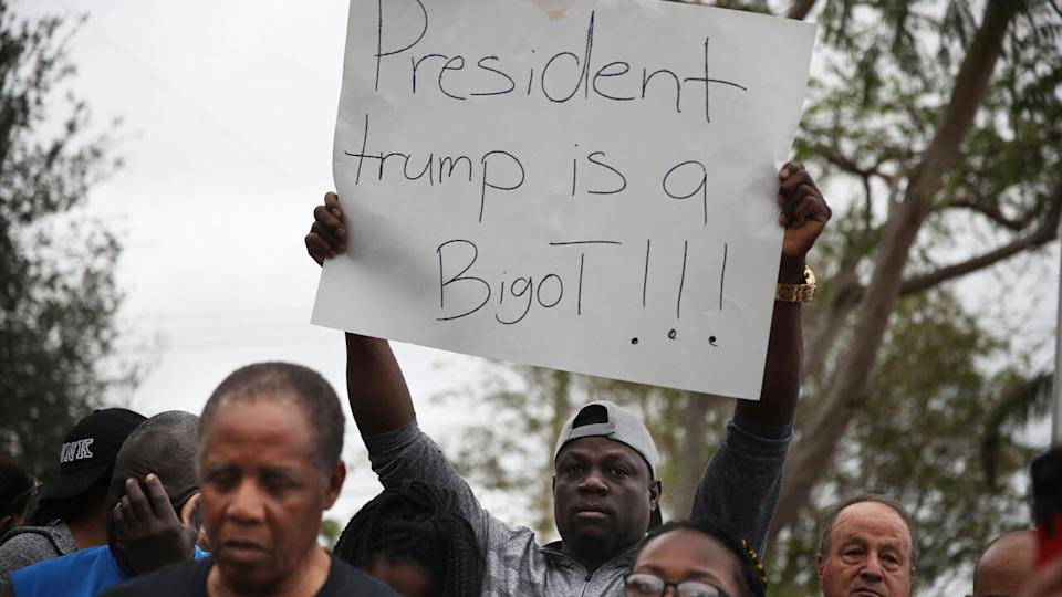 "Jorel Francois holds a sign that reads, ""President trump is a Bigot!!!"" as he joins with others to mark the 8th anniversary of the massive earthquake in Haiti and to condemn President Donald Trump's reported statement about immigrants from Haiti, Africa and El Salvador on January 12, 2018 in Miami, Florida. (Photo by Joe Raedle/Getty Images)"
