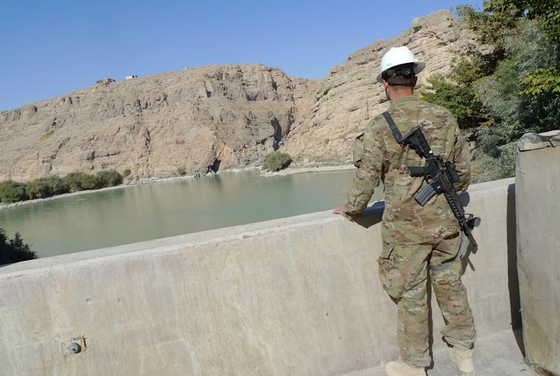 In this Thursday, Nov. 15, 2012 photo, a U.S. Marine looks out at the lake formed by the Kajaki dam in Helmand province, south of Kabul, Afghanistan. The dam is a symbol of the American presence in Afghanistan dating back to the 1950s and the Cold War. The U.S. built the original dam, with a powerhouse added in the 1970s. But before the three turbines could be installed, the Soviets invaded and construction stopped. The dam was still squeezing out a bit of power in 2001 when the U.S. attacked and bombed the dam's power transmission line. (AP Photo/Heidi Vogt)