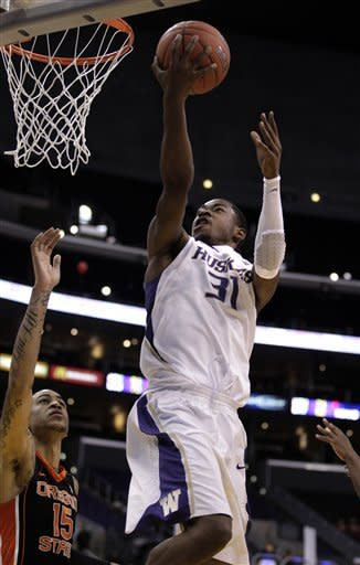 Washington's Terrence Ross, center, puts up a shot as Oregon State's Eric Moreland, bottom left, looks on during the first half of an NCAA college basketball game at the Pac-12onference championship in Los Angeles, Thursday, March 8, 2012. (AP Photo/Jae C. Hong)