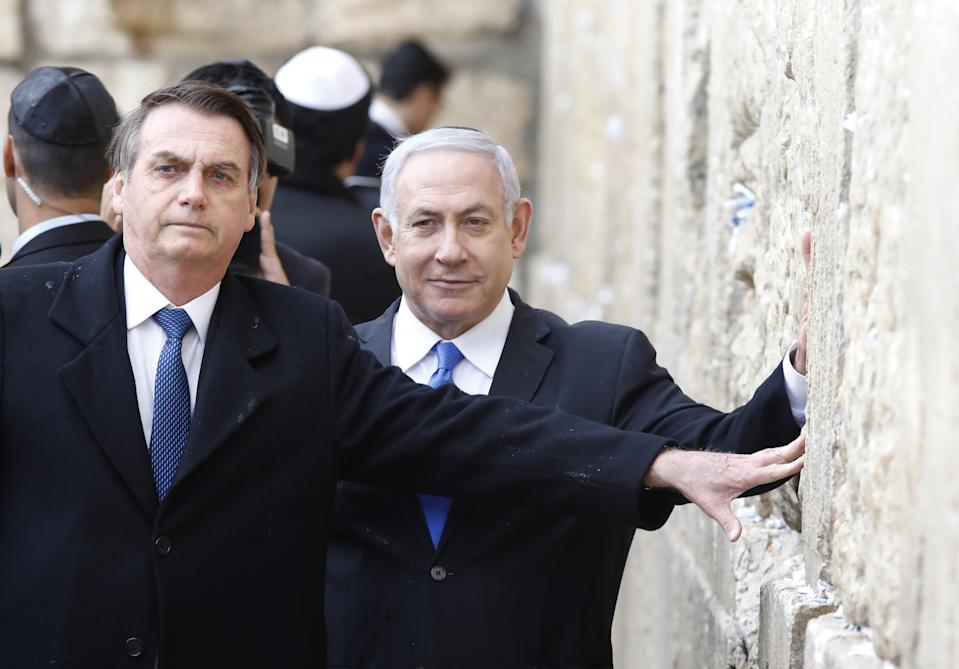 TOPSHOT - Brazilian President Jair Bolsonaro (L) and Israeli Prime Minister Benjamin Netanyahu touch the Western wall, the holiest site where Jews can pray, in the Old City of  Jerusalem on April 1, 2019. - Bolsonaro arrived in Israel just ahead of the country's polls in which his ally Prime Minister Benjamin Netanyahu faces a tough re-election fight. (Photo by Menahem KAHANA / POOL / AFP)        (Photo credit should read MENAHEM KAHANA/AFP via Getty Images)