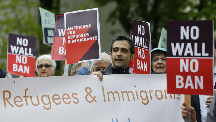 FILE - In this May 15, 2017, file photo, protesters hold signs during a demonstration against President Donald Trump's revised travel ban, outside a federal courthouse in Seattle. Trump appears to be ignoring a deadline to establish how many refugees will be allowed into the United States in 2021, raising uncertainty about the future of the 40-year-old resettlement program that has been dwindling under the administration. The 1980 Refugee Act requires presidents to issue their determination before Oct. 1, 2020, the start of the fiscal year. (AP Photo/Ted S. Warren, File)