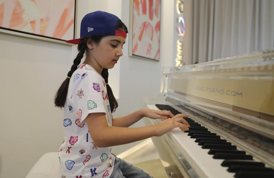 Michelle Rasul plays piano in the lobby of her apartment building in Dubai, United Arab Emirates, Sunday, May 9, 2021. Rasul, a 9-year-old girl from Azerbaijan who lives in Dubai, is scratching her way to the top as a DJ after competing in the DMC World DJ Championship. (AP Photo/Kamran Jebreili)