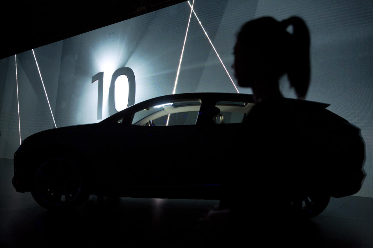 In this April 20, 2018, photo, a woman stands near the silhouette of an electric concept car from auto startup BYTON during a press event held ahead of the Auto China 2018 in Beijing, China. Auto China 2018, the biggest global auto show of the year, showcases China's ambitions to become a leader in electric cars and the industry's multibillion-dollar scramble to roll out models that appeal to price-conscious but demanding Chinese drivers. (AP Photo/Ng Han Guan)