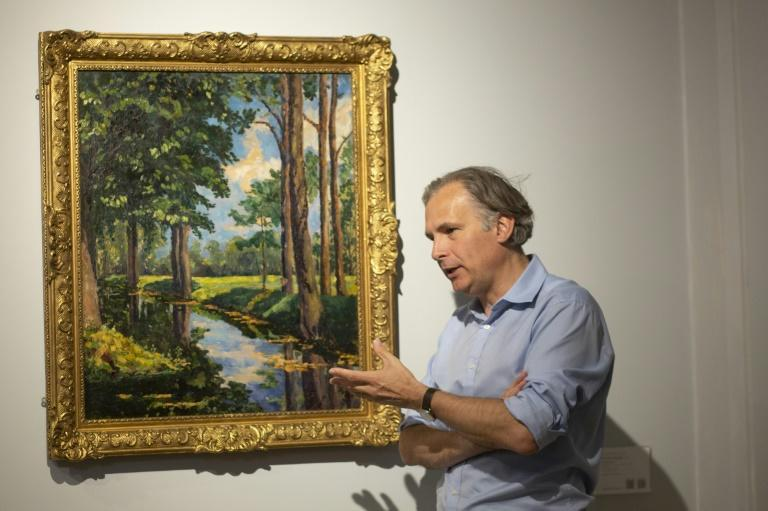 """Jean-Paul Engelen, Deputy Chairman of Phillips auction house, speaks next to """"The Moat, Breccles"""" painting by Winston Churchill and owned by the Onassis family"""