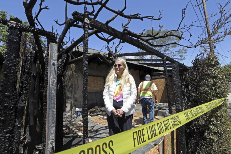 "Gunilla Persson, star of the Swedish television reality show ""Svenska Hollywoodfruar,"" or ""Swedish Hollywood Wives"" poses after a predawn fire severely damaged her home and a neighbor's in the Pacific Palisades area of Los Angeles Thursday, April 13, 2017. (AP Photo/Reed Saxon)"