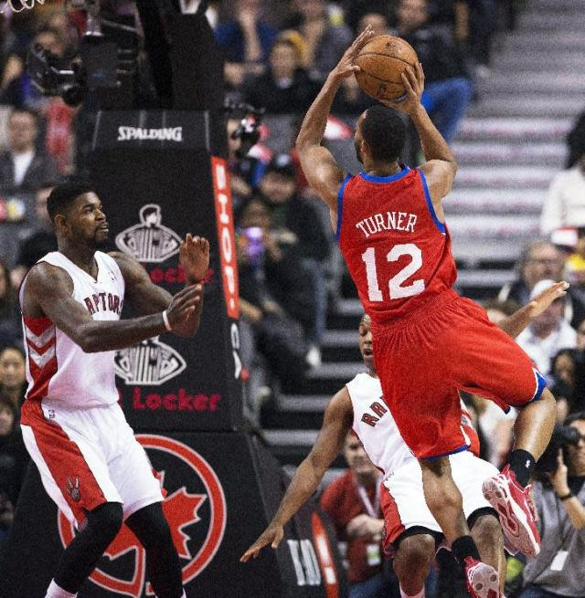 Philadelphia 76ers' Evan Turner, right, goes to the net against Toronto Raptors' Amir Johnson, left, and Kyle Lowry during the first half of an NBA basketball game in Toronto on Friday, Dec. 13, 2013. (AP Photo/The Canadian Press, Aaron Vincent Elkaim)