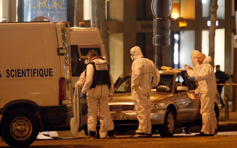 Forensic experts collect evidences from the car belonging to an attacker who killed a police officer on the Champs Elysees avenue in Paris - Credit: AP
