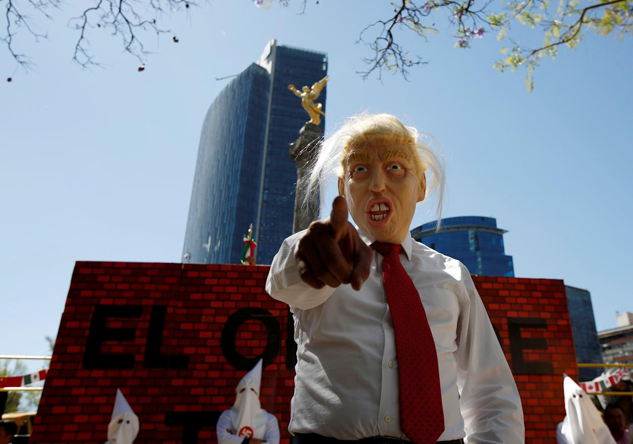 Actors impersonating U.S. President Donald Trump and members of the Ku Klux Klan stage a performance on behalf of a local Mexican political party during a protest against Trump, in Mexico City, Mexico February 20, 2017.   REUTERS/Jose Luis Gonzalez