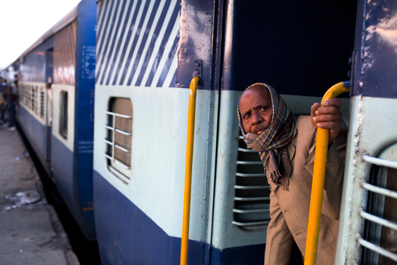 NEW DELHI, INDIA - FEBRUARY 07: A man peers from a carriage prior to departure from the Nizamuddin Railway Station on February 07, 2012 in New Delhi, India. The Nizamuddin Railway Station serves as the main station connecting all major cities, and is served by Northern Railways. The state-owned Indian Railways runs 12,000 trains a day, covers 39,000 miles of track, employs 1.4 million people and is the world's second biggest rail network under single management. (Photo by Daniel Berehulak/Getty Images)