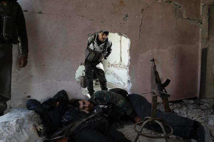 Syrian rebel fighters from the Failaq al-Rahman brigade rest during a lull in fighting against regime forces in Bala, a town on the outskirts of Damascus, on February 28, 2016 (AFP Photo/Abdulonam Eassa)