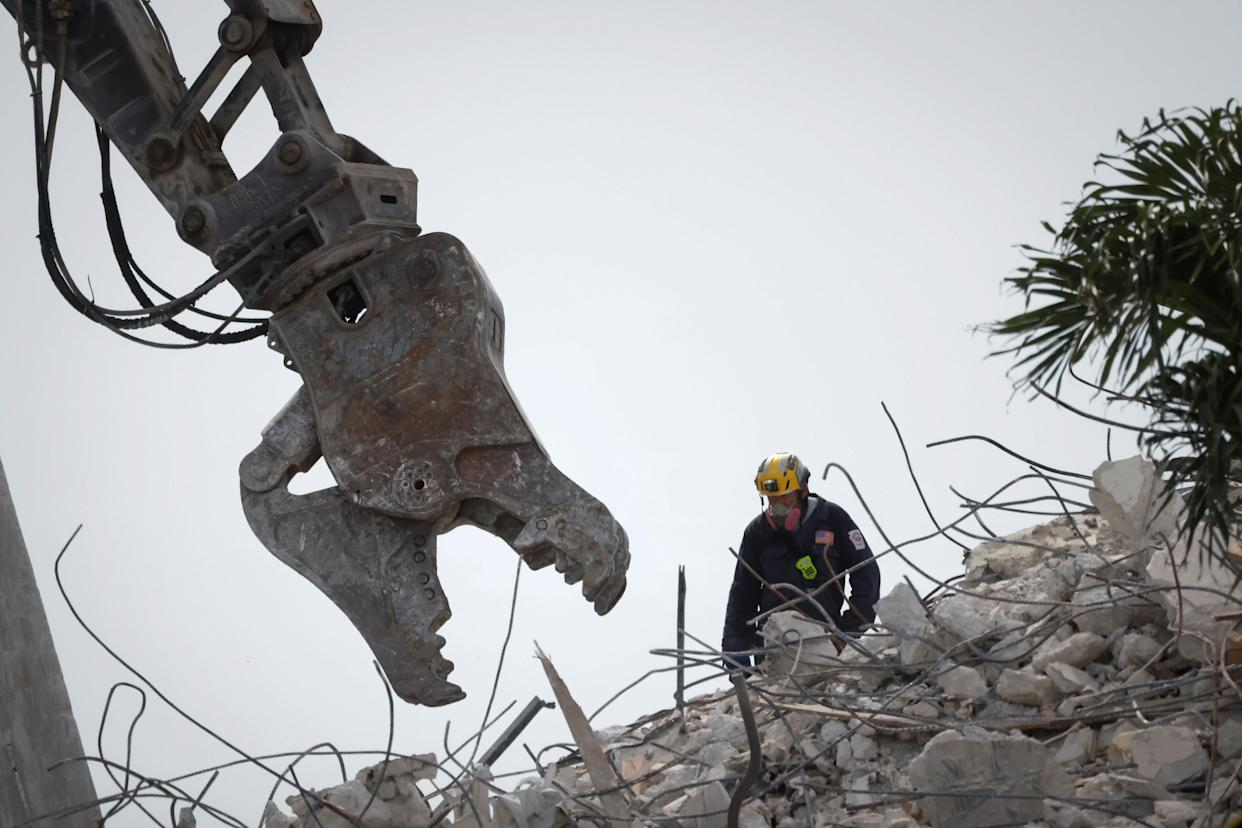 A rescue worker is seen on the pile of the collapsed buidling in Surfside, Fla,, Monday. (Marco Bello/Reuters)