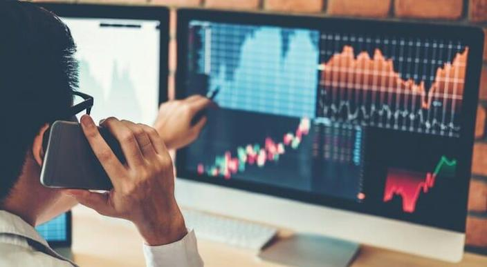 Image shows an investor speaking on the phone while pointing to a computer screen with data analysis on investments. Bitcoins futures can be another possibility for cryptocurrency investors to consider.